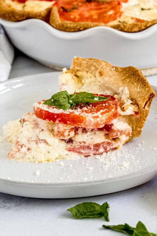 Slice of tomato pie on a white dish