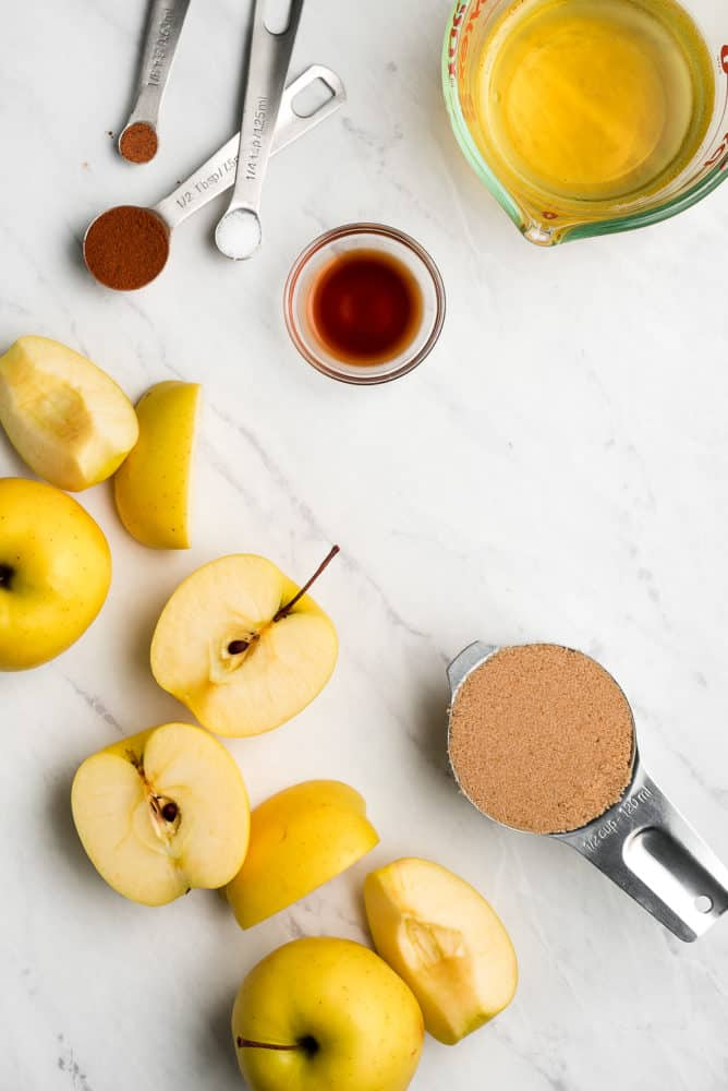 Apples cut in half and quarters, teaspoons of spices, a small bowl of vanilla extract, a liquid measuring cup of apple cider, and a measuring cup of brown sugar.