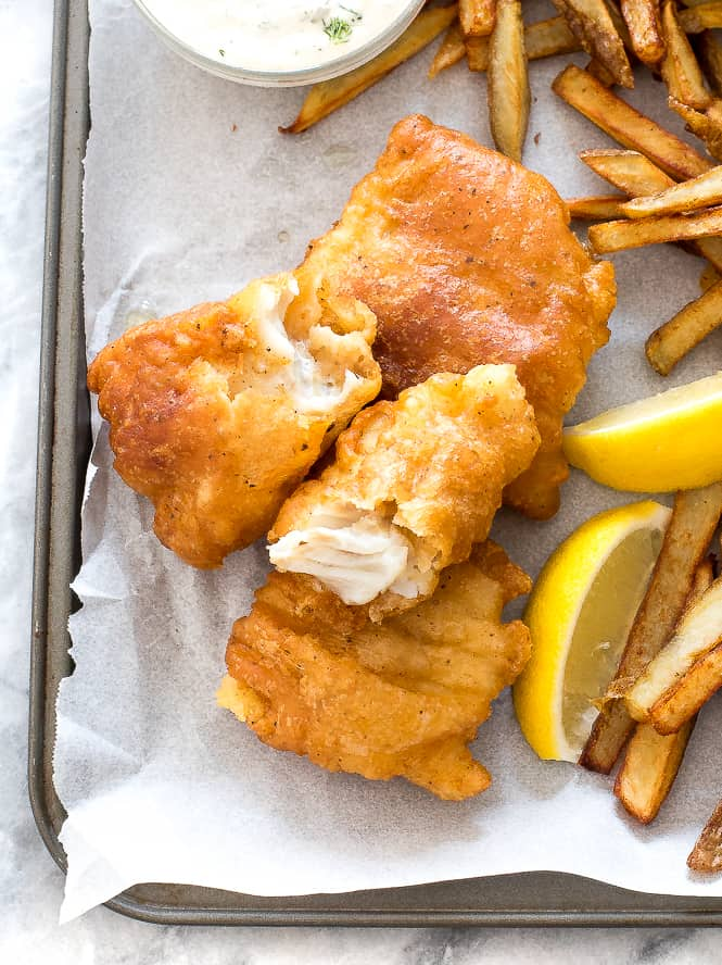 Fish and chips on a sheet pan with parchment paper overtop with French fries and lemon slices on the side.