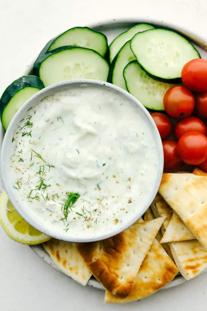 Close up on tzatziki sauce in a bowl on a veggie platter with pita.
