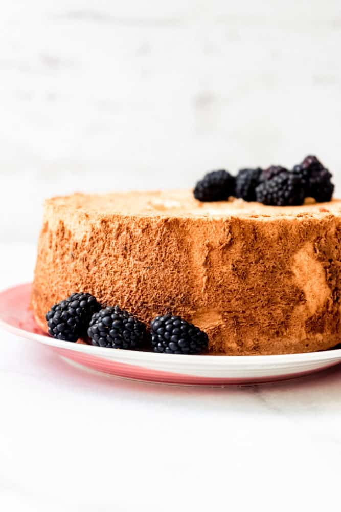 An angel food cake on a plate with blackberries.