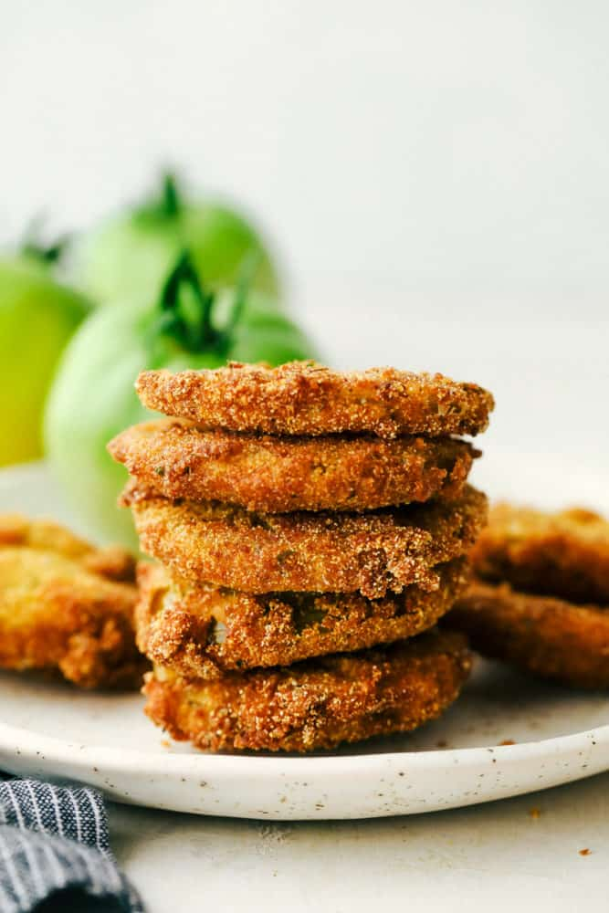 Stack of fried green tomatoes on a white plate.