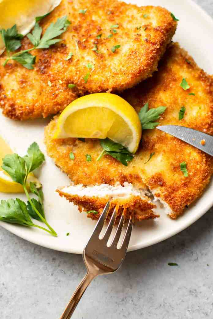 pork schnitzels on a plate with lemon wedges and one schnitzel cut into showing a bite on a fork
