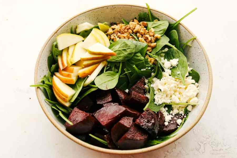 Pears, beets, spinach, feta and nuts in a bowl.