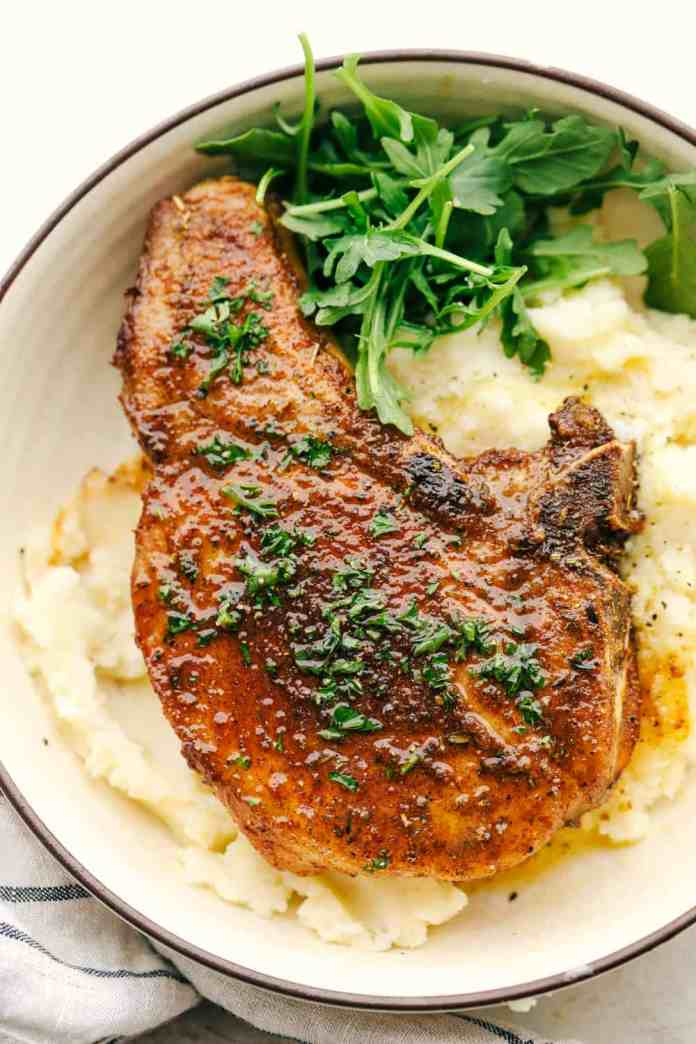 Juicy and tender air fryer Pork chops on a bed of mashed potatoes.