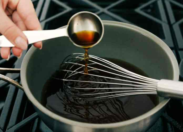 Adding ingredients to a saucepan to make maple syrup.