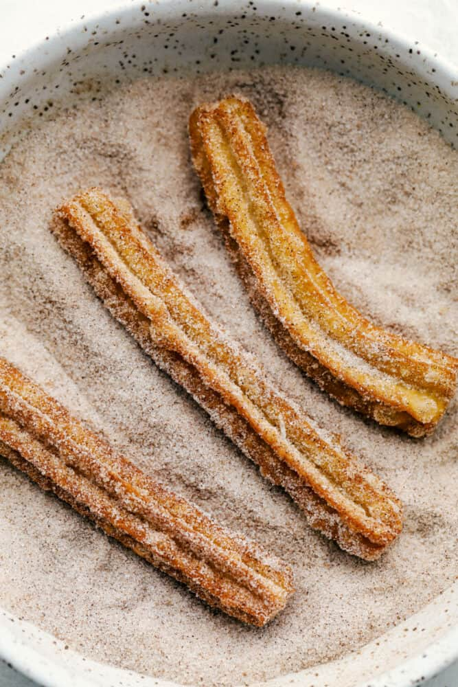 Rolling the Churros in cinnamon and sugar.