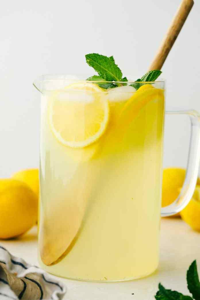 A pitcher of homemade lemonade with lemons.