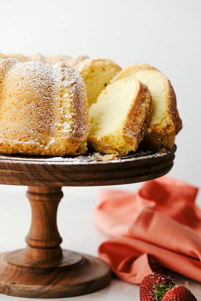 Sour cream pound cake sliced sitting on a pedestal stand.