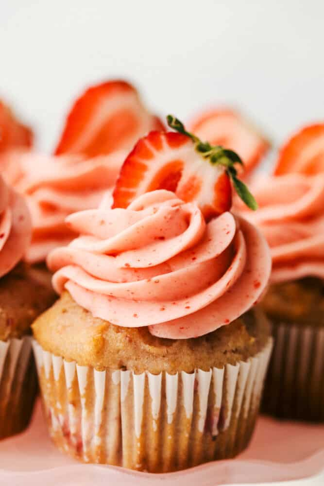 A strawberry cupcake with swirled frosting and a strawberry on top.