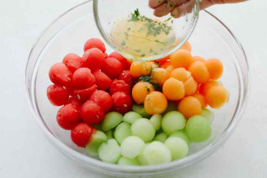 A bowl filled with watermelon, honeydew and cantaloupe scooped in small sizes with dressing being poured on them.