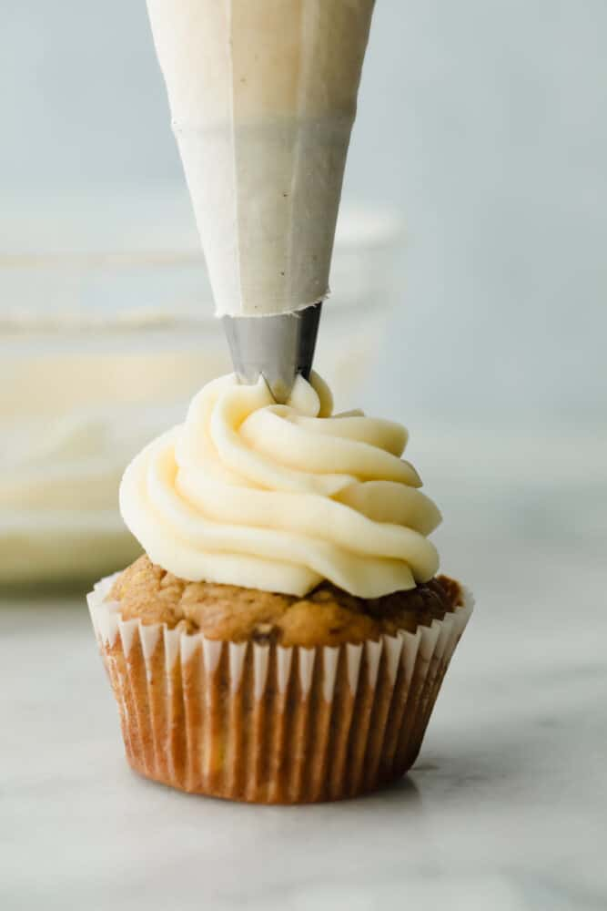 Cream cheese frosting being piped onto a cupcake.