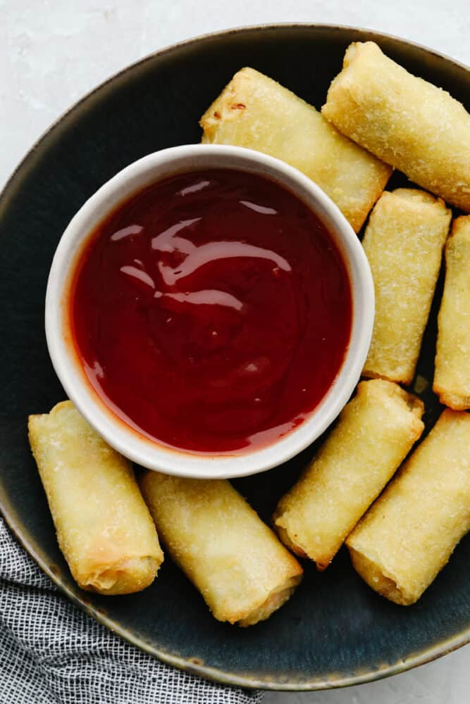 A platter with egg rolls and sweet and sour sauce.