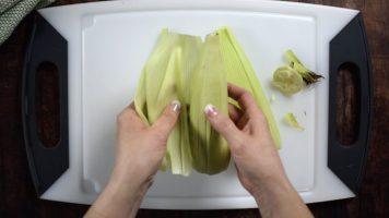 Peel corn, preserving the husks.