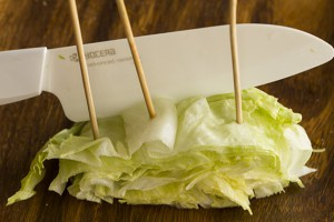 Taking your knife and leaving an inch from the uncut side of the lettuce, cut off the part with the toothpick inserts. The toothpick inserts should now be all in a row, and the large wedge should have separated from the main head off lettuce.