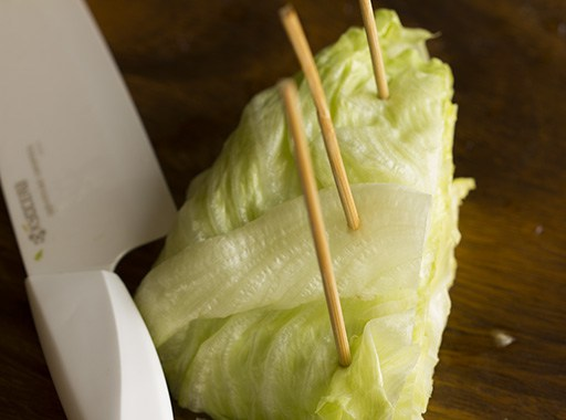 Then, take three, (if you have a larger head of lettuce then take four or five) long wooden barbecue sticks, (they should be larger than cocktail toothpicks - about 4 to 5 inches long) and leaving an inch from the side of the cut side of the lettuce, poke them at 1 and 1/2 inches interval. This is done 90 Deg from the cut side of the lettuce, and not parallel to the root and cut side of the lettuce.
