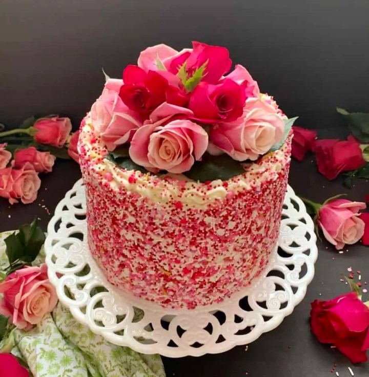 Easy moist vanilla Cake recipe Topped with beautiful roses on a decorative cake stand