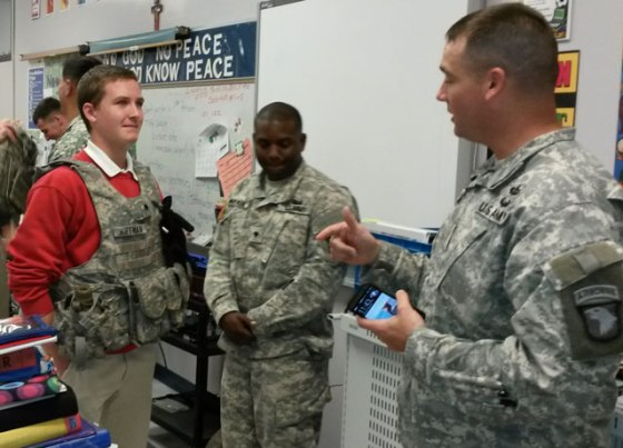 Aric Lyons, an eighth-grader at St. Stephen Martyr School, left, tried on some army gear and spoke with Specialist Huffman, center, and Major Matthew Childers, right, May 19. Soldiers from Fort Campbell visited with students and presented the school with a certificate of appreciation for their work with Operation Support Peace, a stewardship program that supports military families. (Photo Special to The Record)