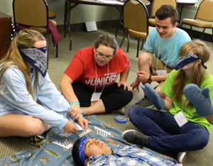 Teenagers, from left to right, Kimberly Malone, Kacie Gaekle, Jack Wolfram and Tessa Grissom and Jason Patrana, foreground, worked together to assemble a puzzle during a team-building activity at the annual Christian Leadership Institute held July 6 to 10 at the Flaget Center.