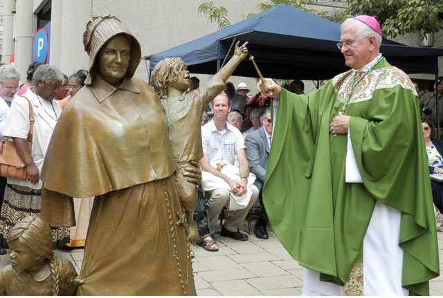 Archbishop Joseph E. Kurtz sprinkled holy water over the newly unveiled statue of Mother Catharine Spalding outside the Cathedral of the Assumption July 26. (Record Photo by Ruby Thomas)