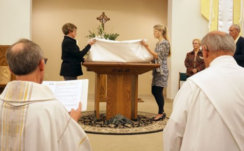 Pat Riney and Louise Walker, St. Pius parishioners, remove and fold the altar cloth as part of the concluding rite.