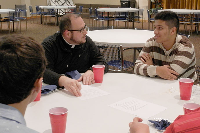 Father Jason Harris spoke to Johann Pybus during a group discussion at the St. Andrew Dinner Dec. 6. The discernment dinner was sponsored by the Vocations Office and hosted by St. Patrick Church in Eastwood. (Record Photo by Ruby Thomas)