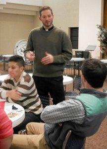 Father Michael Wimsatt, director of the Vocation Office, gave the young men directions for a group discussion during the St. Andrew Dinner. (Record Photo by Ruby Thomas)