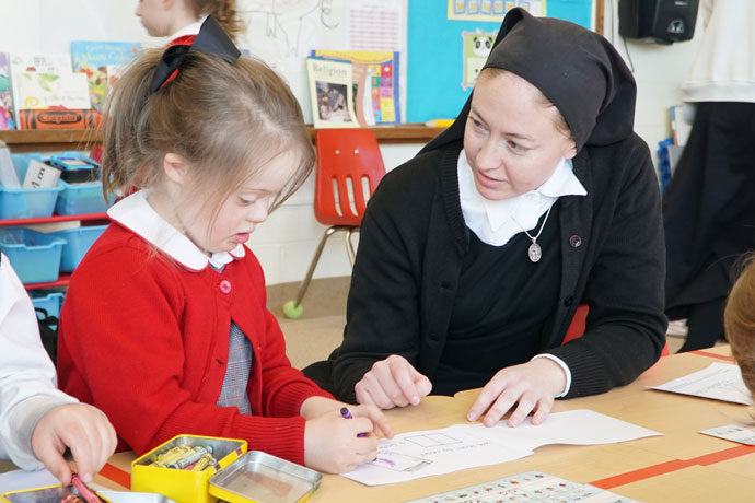Sister of the Fiat Caryn Crush worked with preschool student Lola Rosenbaum Jan. 29 at Immaculata Classical Academy, 3044 Hikes Lane. Rosenbaum is one of 15 special-needs students who share the school's classrooms with typical pupils. The Sisters of the Fiat is a public association of the faithful that ministers to individuals with special needs. (Record Photo by Ruby Thomas)