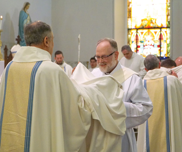 The newly-ordained Deacon Martin, below, is assisted by Father John Burke, pastor of Good Shepherd, in the vesting of the dalmatic and stole.