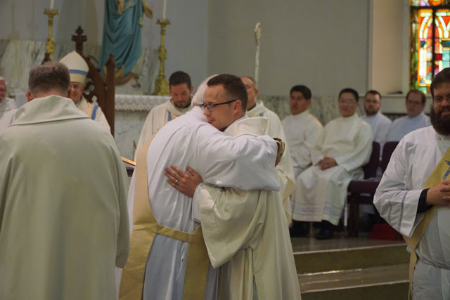 The newly-ordained Deacon Casey Sanders, above, shared a kiss of peace with one of his fellow deacons after the rite of ordination March 19 at Good Shepherd Church.