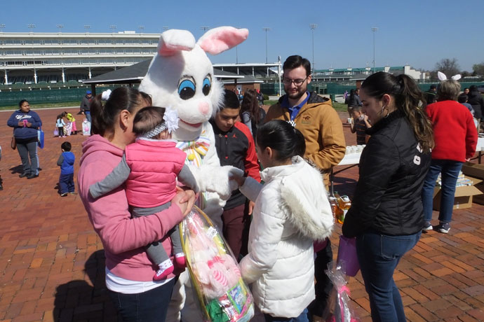 Photos Special to The Record From darkness into light More than 100 children of race track workers, above, participated in an Easter egg hunt hosted by the Kentucky Race Track Chaplaincy March 26 in the infield at Churchill Downs. The Easter Bunny visited, from left, Alicia Gallegos, holding Mia Chavez; Brandon Gallegos; Julissa Quinteros; Chris Wong, associate chaplain of Kentucky Race Track Chaplaincy; and Diana Gallegos. The interdenominational Christian race track ministry, which includes local Catholics, serves workers at Kentucky's race tracks and horse training centers. In the photo below, Hunter Johnson, an eighth-grader at St. Nicholas Academy, carried the cross during a Good Friday procession on New Cut Road March 25. The students later prayed the Stations of the Cross, a tradition at St. Nicholas.