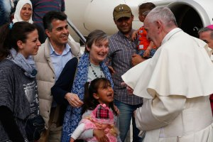 Pope Francis greeted Syrian refugees he brought to Rome from the Greek island of Lesbos, at Ciampino airport in Rome April 16. The pope concluded his one-day visit to Greece by bringing 12 Syrian refugees to Italy aboard his flight. (CNS Photo by Paul Haring)