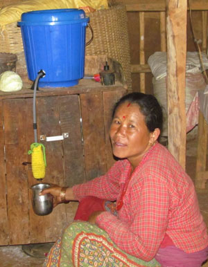 A Nepalese woman collects clean water from a water purification system provided by Water With Blessings after deadly earthquakes in Nepal.