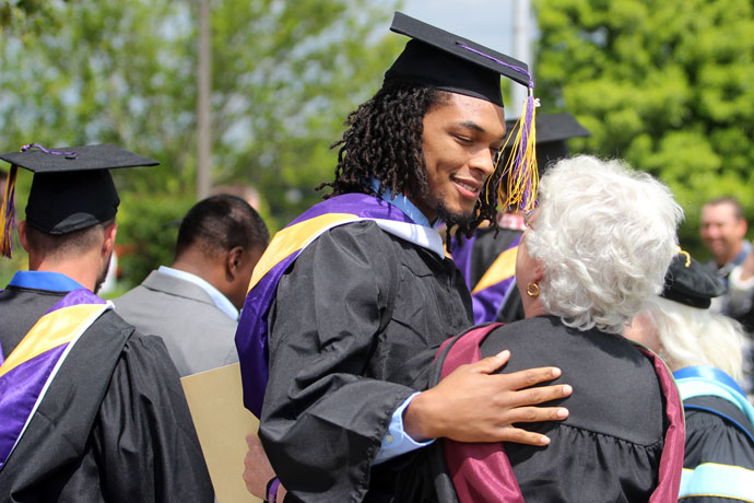 Christian Johnson hugged professor Peggy Tillman after St. Catharine College's graduation ceremony May 14. (Photo Special to The Record)
