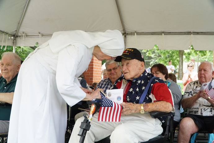Little Sister of the Poor Mother Paul places a flag pin on the shirt of George Hauck, a World War II veteran and long-time volunteer for the Little Sisters, at the Flag Day ceremony June 14.