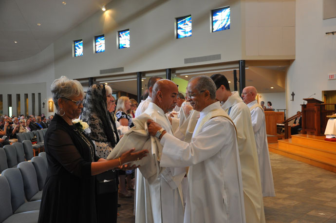 Deacon James R. Turner, right, assisted the newly-ordained Deacon Anthony T. Brown in vesting with the dalmatic and stole. Deacon Brown's wife, Naomi Marie Brown, far left, and Julie Fagan, the wife of Deacon Richard J. Fagan, assisted.