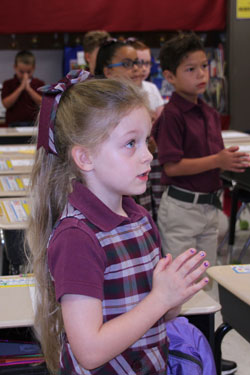 Charlotte Cloud, a first-grader at John Paul II Academy, prayed on the first day of school Aug. 11. (Photo Special to The Record by Sally Lynch)