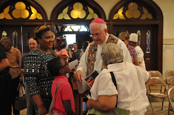 Archbishop Joseph E. Kurtz greeted, from left, Dorice Firmin, holding Dorienne Firmin, Armonte Snodgrass and Gail Aubespin-Richardson at prayer service held Sept. 9 at St. Martin de Porres Church, 3112 W. Broadway.