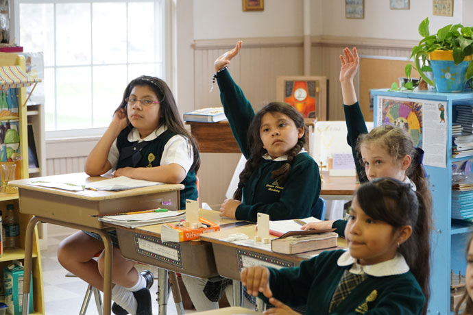 Students at Corpus Christi Classical Academy, from left, Ava Crawford, Fatima Camposeco, Anna Cozzens and Jacquelin Olvera, listened to their teacher during a lesson in April. The school in Simpsonville, Ky., was recognized by the Archdiocese of Louisville as an independent Catholic school last winter. (Record file photo by Ruby Thomas)