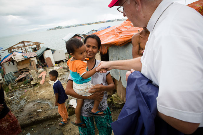 Archbishop Joseph E. Kurtz, president of the U.S. Conference of Catholic Bishops, greets a child in Anibong, a community in Tacloban, Philippines, Feb. 4, 2014, following the devastation caused by Typhoon Haiyan. Archbishop Kurtz counts his pastoral visit to the Philippines as a highlight of his three-year tenure as president of the bishops' conference. (CNS photo/Tyler Orsburn)