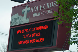 Holy Cross High School has hailed 2005 alumnus Nicholas Rodman a hero after he died March 29 from injuries he sustained while pursuing a suspect. The school has honored him in several ways, including with this message on the school's sign on Dixie Highway. (Record Photo by Ruby Thomas)