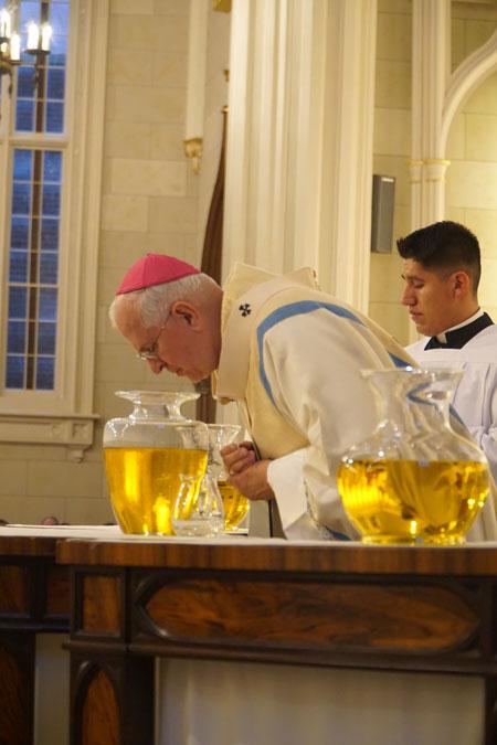 Archbishop Kurtz breathed on the sacred chrism.