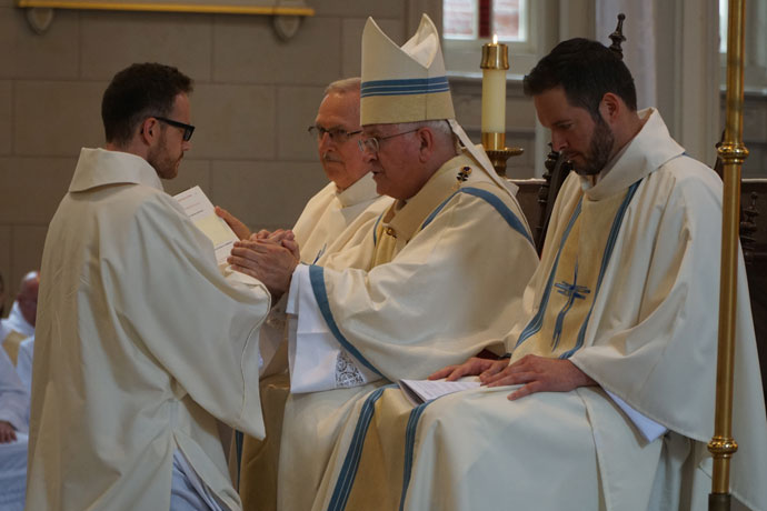 Father Casey Sanders knelt before Archbishop Kurtz and promised respect and obedience to the archbishop and his successors.