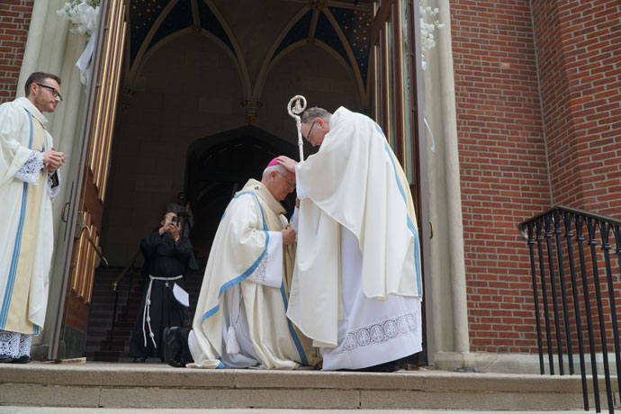 Father Michael Martin blessed Archbishop Joseph E. Kurtz on the steps of the Cathedral of the Assumption after ordination May 27. Father Casey Sanders looked on.