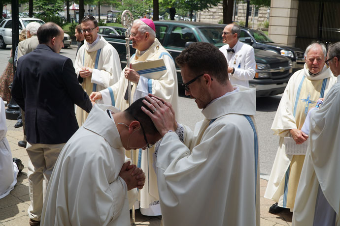 After the ordination, Father Casey Sanders offered a blessing to Deacon Kien Nguyen.