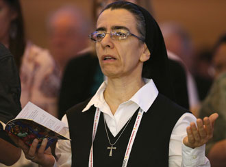 """A woman religious prays July 2 during the """"Convocation of Catholic Leaders: The Joy of the Gospel in America"""" in Orlando, Fla. Leaders from dioceses and various Catholic organizations gathered for the July 1-4 convocation. (CNS photo/Bob Roller)"""
