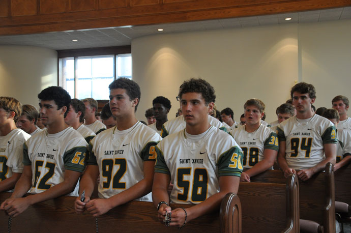 Players from St. Xavier High School pray the rosary at the July 26 gathering at Holy Family Church.