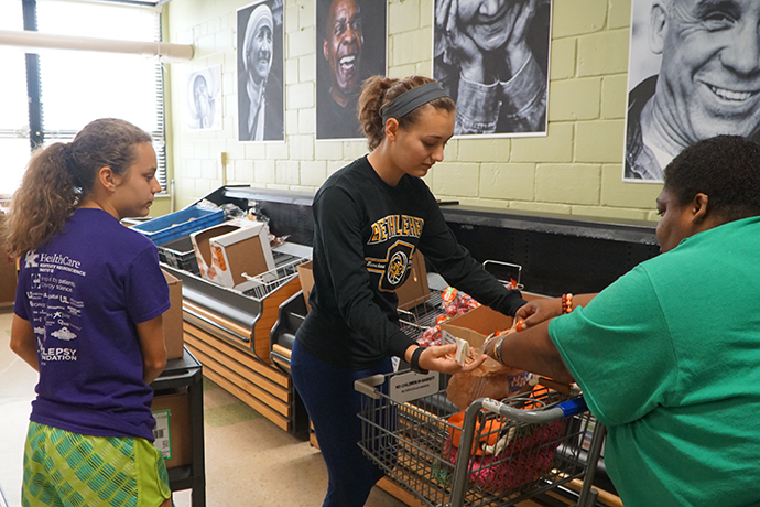 Rebecca Lee, left, an eighth-grader at St. Joseph School in Bardstown, Ky., and Lauren Lee, a junior at Bethlehem High School in Bardstown, assisted a client at the Bread for Life community food pantry on Oct. 7. Students from Bethlehem staff and manage the food pantry on Saturdays. (Record Photo by Jessica Able)