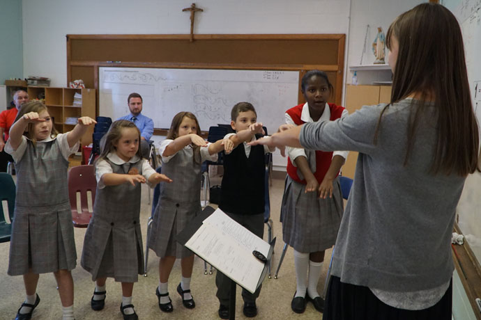Music teacher Mary Perkinson lead third-graders, from left, Elena Michalak, Kiera Vincent, Kolton Renner and Stephanie Rhodes during choir class at Immaculata Classical Academy Oct. 19. Between 15 and 20 percent of the school's students have special needs. (Record Photo by Ruby Thomas)
