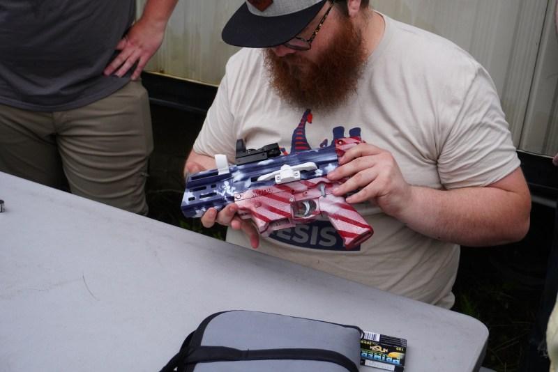 Match officials inspect a 3D-printed gun
